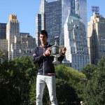 Постер, плакат: Ten times Grand Slam champion Novak Djokovic posing in Central Park with championship trophy