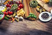 Italienische und mediterrane Lebensmittelzutaten auf alten hölzernen Hintergrund