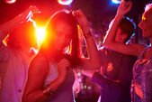 Belle ragazze ballare in discoteca su sfondo di ragazzi