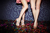 Legs of two girls dancing in night club, close up