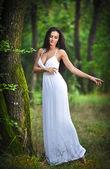 Schöne junge Dame trägt ein elegantes langen weißes Kleid genießen die himmlische Lichtstrahlen auf ihrem Gesicht in die verzauberte Wälder. Langes Haar Brünette Frau aussah, als eine glamouröse Prinzessin im Wald