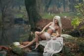 Schöne junge Dame sitzt nahe Fluss in die verzauberte Wälder. Sinnliche Blondine mit weißen Kleidung provozierend posiert im herbstlichen Park. Mädchen mit Märchen im Herbst Landschaft suchen. Romantische Frau nahe See