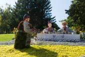 Floral display of a servant serving tea to a man and woman seated at a table with the clothing formed of fresh flowers in an exhibition of creative art outdoors in a park