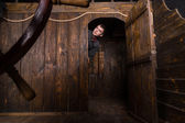 Young Man Peering Out From Cabin of Wooden Ship