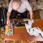 Постер, плакат: Senior Man Mending Pants with Sewing Machine