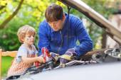 Young father teaching his little son to repair motor oil in fami