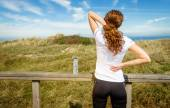 Back view of athletic young woman in sportswear touching her neck and lower back muscles by painful injury, over a nature background. Sport injuries concept