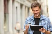 Man online mit einer Kreditkarte und einem Tablet-Kauf