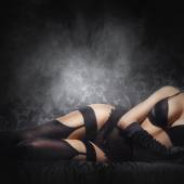 Erotic photo of young and beautiful woman in sexy underwear over smoky background