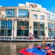 Постер, плакат: Hard Rock Cafe on the Singelgrachtkering Canal with boat in amsterdam