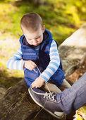 Chlapeček je vázání boty svého otce