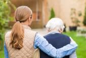 Giovane badante a piedi con la donna anziana nel parco