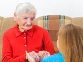 Giovane medico dando mani aiutando per donna anziana