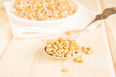 Sprouted wheat seeds on spoon and wooden background, close up, selective focus
