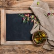 Постер, плакат: Olives and olive oil with menu board rustic setting