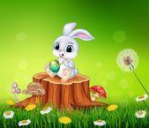 Kreslený Velikonoční zajíček malovat vajíčka na pařezu v letní sezóně pozadí