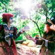Постер, плакат: Young woman and man in the image of the Hatter and the Red Queen from the fairy tale about Alice