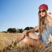 Venku ráno záběr hippie dívka sedí na louce
