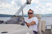 Ältere Männer fahren ein Ponton-Boot auf einem See