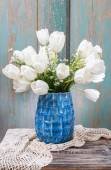 Kytice bílých tulipánů v modré keramická váza