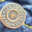 Постер, плакат: Closeup of Levi Strauss button on blue jeans