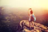 Turista na vrchol hory s smartphone