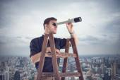 Young businessman looking for future opportunities through the spyglass standing on stairs.  Cloudy sky and city around
