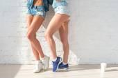 Sportovní dlouhé sexy nohy ze dvou krásných žen džíny kraťasy městské neformální pouliční styl módy slunečný den stojící u zdi
