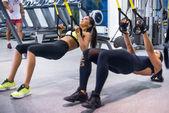 Donna che si esercita con cinghie di sospensione nel fitness club o palestra