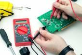 Elektrikář kontroluje elektronický hardware s multimetr v