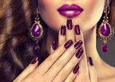 ženská tvář s fialovým manikúra