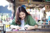 Okouzlující Asijská dívka sedí u dřevěného stolu a čtení knihy