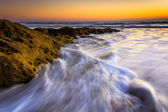 Rocks and waves in the Atlantic Ocean at sunrise in Palm Coast,