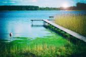 Spring sunrise over blue lake - retro effect