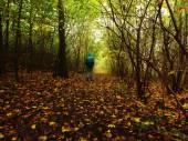 Man walking in dark misty forest in autumn