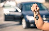 Mužská ruka hospodářství moderní klíčky připraven pro pronájem - koncepce dopravy s automobil z druhé ruky, prodej a obchod