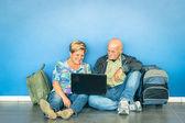 Šťastný starší pár sedí na podlaze s notebookem čekání na letadlo na letišti - koncepce aktivních seniorů a interakce s novými technologiemi - cestovní životní styl bez omezení věku
