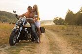 Muscular man with a beautiful woman on a motorcycle middle of a field road
