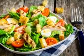 Caesar salad with croutons, quail eggs, cherry tomatoes and grilled chicken