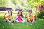 Tre bambini nel parco che soffia bolle di sapone e divertirsi