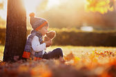 Ragazzo adorabile con lorsacchiotto nel parco il giorno di autunno