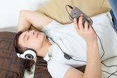 Muž pád spát poslech hudby přes smartphone s headphon