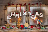 Outdoor christmas window decoration with red candles and text.