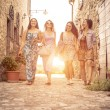 Постер, плакат: Group of girls walking in a historic center in italy
