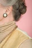 Starší žena nosí šperky