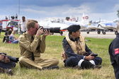 Men in vintage pilot uniforms taking pictures with cameras with the swiss Pilatus Warbird aerobatic team P3 Flyers in background