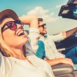 Постер, плакат: Woman and her boyfriend in convertible