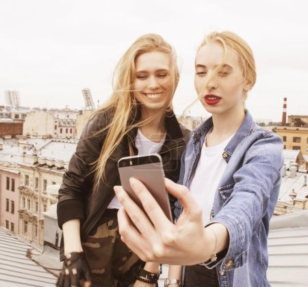 Two cool blond real girls friends making selfie on roof top, lifestyle people concept