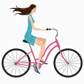Beautiful girl in dress rides a bicycle