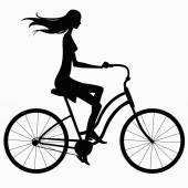 Silhouette girl in dress rides a bicycle